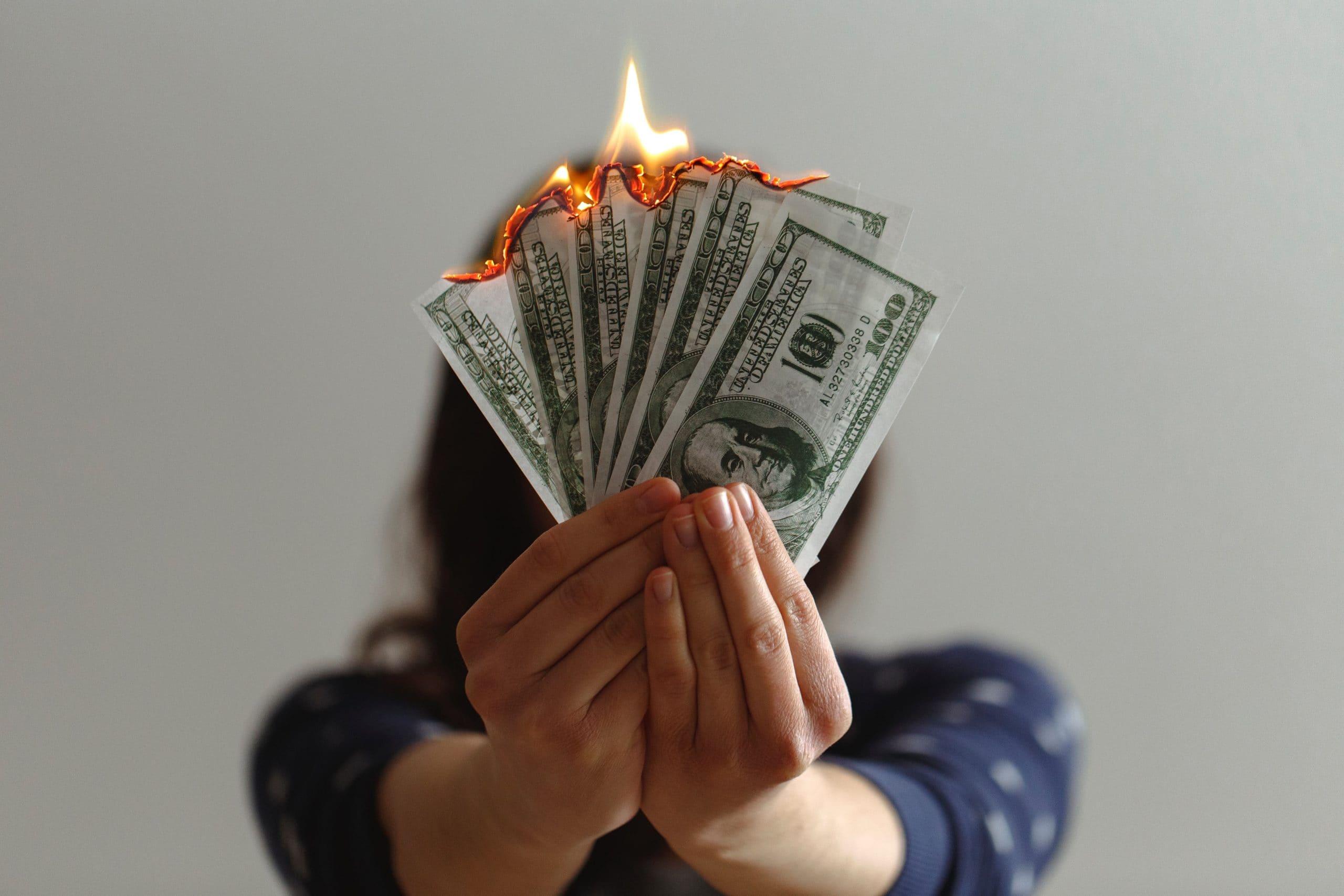お金を燃やす女性